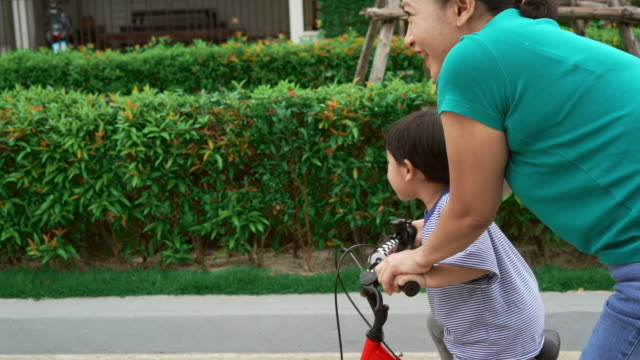 Asian boy cycling bicycle with mother video