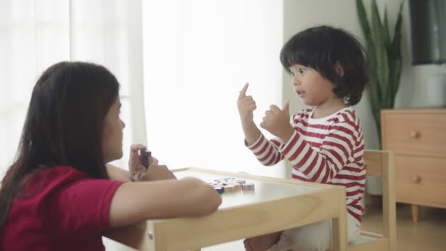 asian boy doing homework with mother in the morning - two students together asian video stock e b–roll