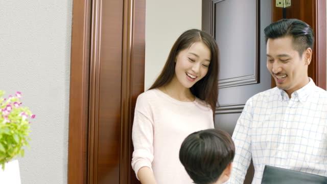 アジアの少年の父親と母親の別れの挨拶と学校に行く - 分離点の映像素材/bロール