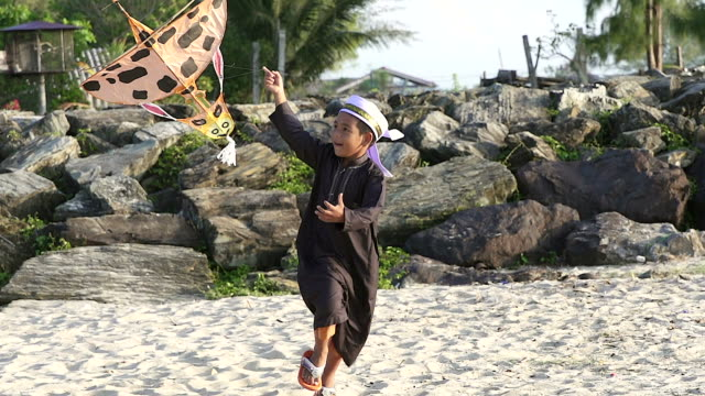 Asian boy playing with his traditional kite.He running on the beach.