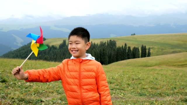 Asian boy playing with windmill in grassland