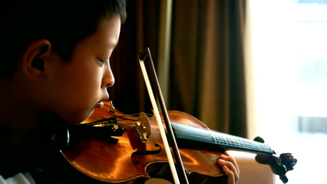 asian boy plays violin at home video