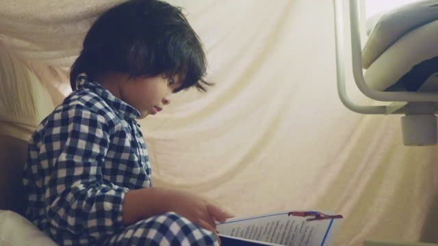 Asian boy reading a fairy tale with flashlight under a blanket fort