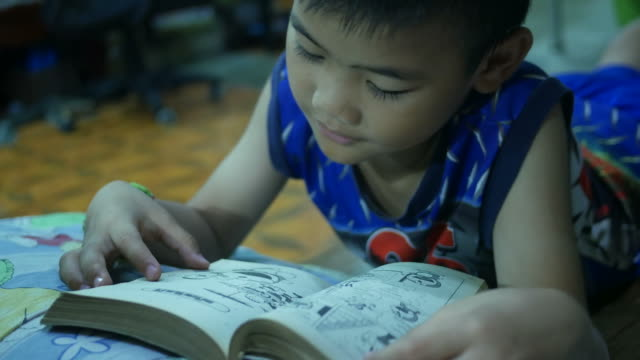 Asian boy reading book in bedroom Asian boy reading book in bedroom wisdom stock videos & royalty-free footage