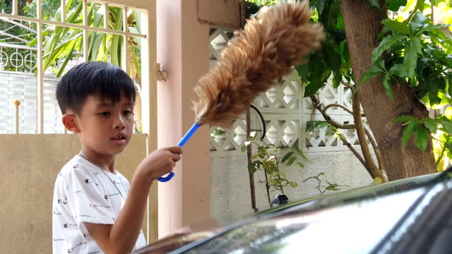Asian boy removing dust from parent's car