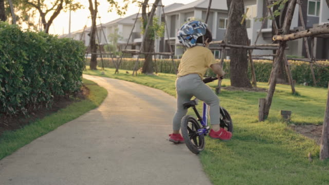 Asian boy riding a bicycle at garden video