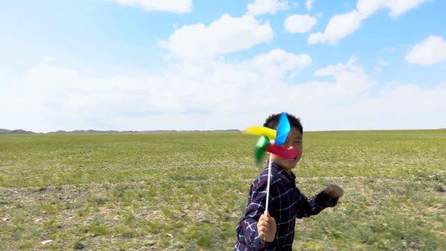Asian boy running with windmill in grassland