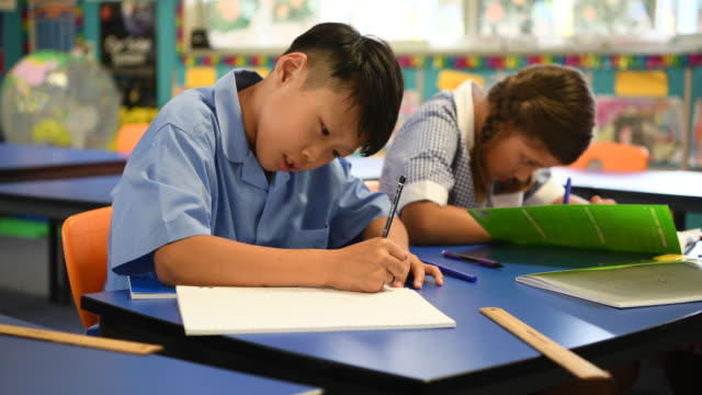 Asian boy sitting at desk and writing in his school book video