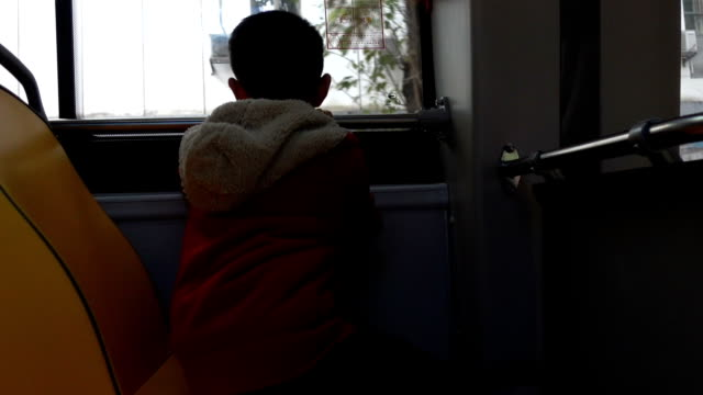 asian boy sitting in bus - scolaro video stock e b–roll