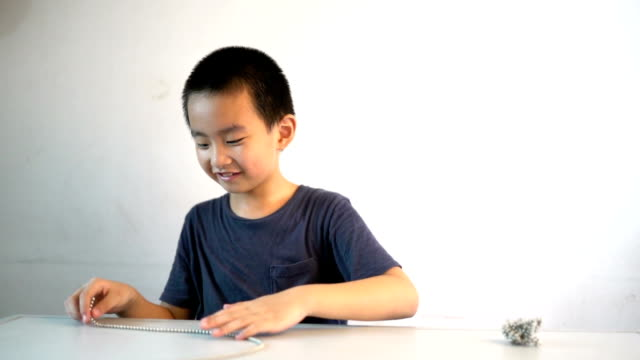 Asian boy sitting infront of table playing magnetic beads video