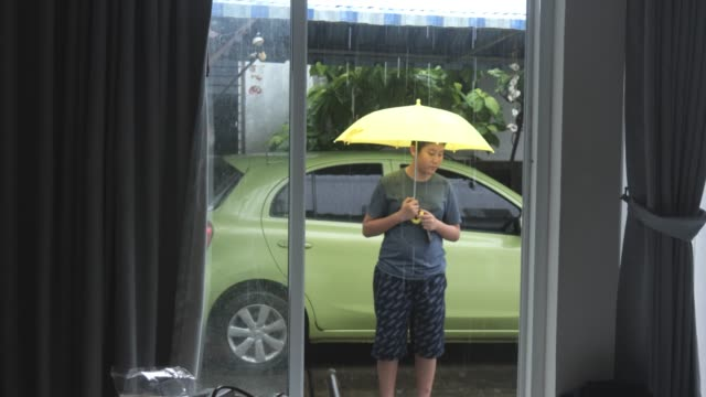 Asian boy using yellow umbrella in raining day and walk in the house.