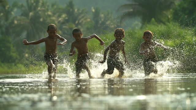 asian boys having fun playing in the river with splashing water together.(slow motion) - children video stock e b–roll