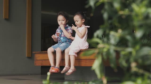asiatische bruder und schwester sind auf dem flur snack essen. - 2 3 jahre stock-videos und b-roll-filmmaterial