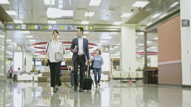 空港でアジアのビジネス同僚とシニアカップル - 乗客点の映像素材/bロール