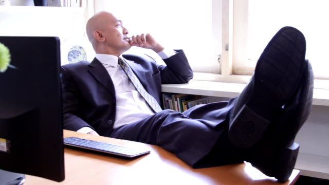Asian business executive thinking at desk video