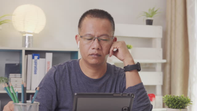 Asian business man aged 40-50 years talking with partner in video conference.man using phone or smartphone for online meeting in video call มDuring the coronavirus to maintain social distance