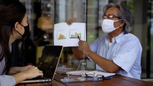 Asian business man and woman discussing in coffee shop with masks on Young Asian business woman discussing business talk with senior business man in medical face masks with table shield to prevent Covid-19 coronavirus. Social distancing and new normal lifestyle shield stock videos & royalty-free footage