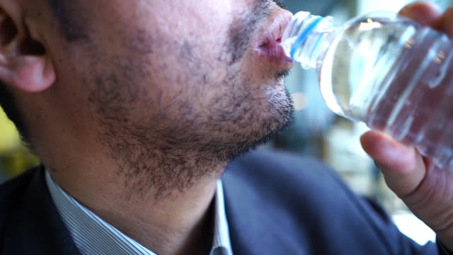 Asian business man drinking water from bottle
