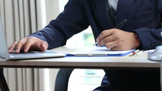 Asian Business man Manager assis cale stylo pour signant demandeur remplissage documents rapports papiers société formulaire ou en vous inscrivant réclamation sur le bureau. Document rapport et business busy Concept - Vidéo