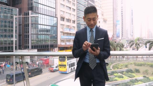asiatiska affärsman använder en mobiltelefon - kinesiskt ursprung bildbanksvideor och videomaterial från bakom kulisserna