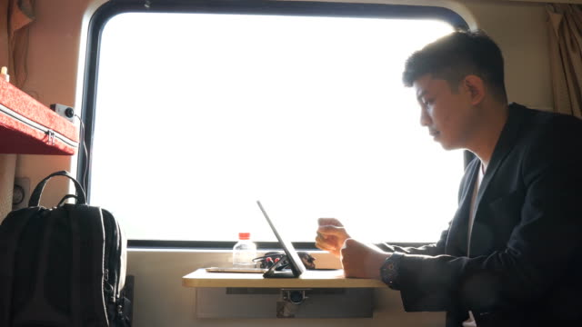 Asian business man using mobile smartphone and digital tablet in train video