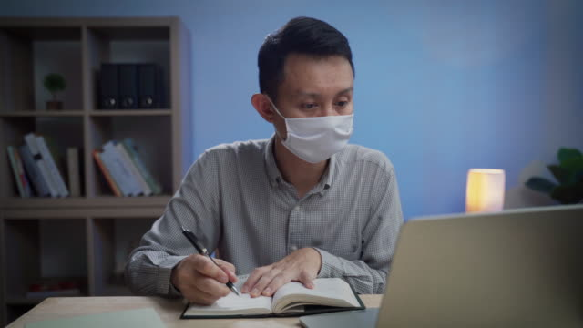 Asian business man wearing protective face mask writing on notebook working late night at office