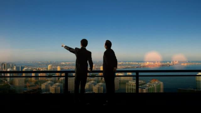 アジア ビジネス パートナー立って・都市の上に未来を探しています。 - 屋根点の映像素材/bロール