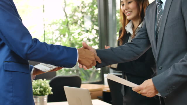 Asian Business people deal a business project together video