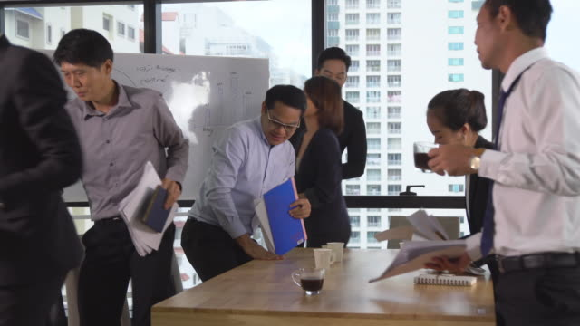 Asian business people finishing meeting and leaving from modern workplace