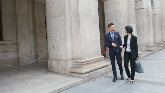 Asian Business People Walking Through the City