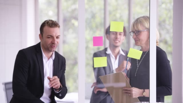 Asian business team planning business strategy with adhesive note