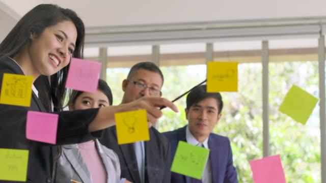 stockvideo's en b-roll-footage met aziatische team aandeel bedrijfsidee op plastic bord - marketing planning