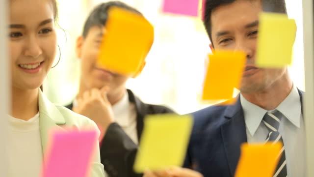 asian business team standing talking work in office room - post it notes filmów i materiałów b-roll
