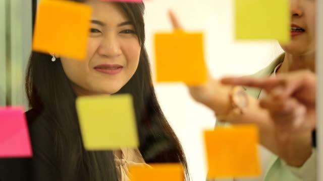 asian business team standing talking work on paper in office room - post it notes filmów i materiałów b-roll