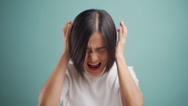 Asian business woman angry and screaming standing isolated over beige background. 4K video video