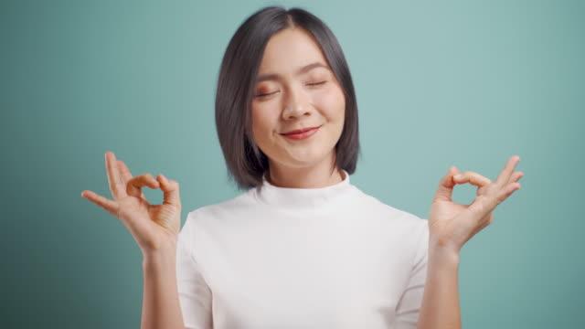 la donna d'affari asiatica si calma, respira profondamente meditando tenendo le mani in un gesto yoga isolato su sfondo blu. video 4k - braccio umano video stock e b–roll