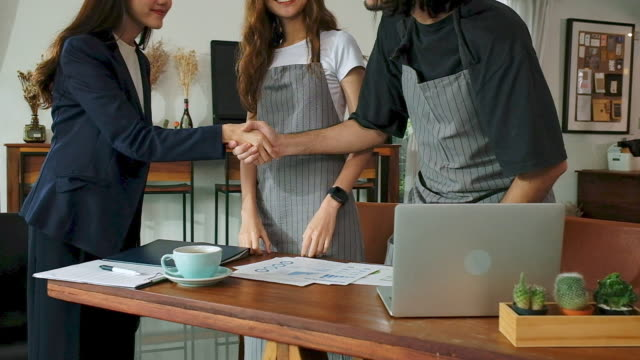 Asian business woman handshake with cafe owner before giving advice about financial planning for small business, close up, slow motion