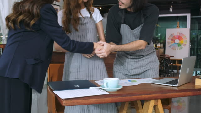 Asian business woman handshake with cafe owner before giving advice about financial planning for small business