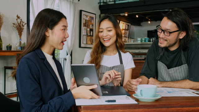 Asian business woman holding digital tablet to explain about financial planning for small business with coffee shop cafe owner