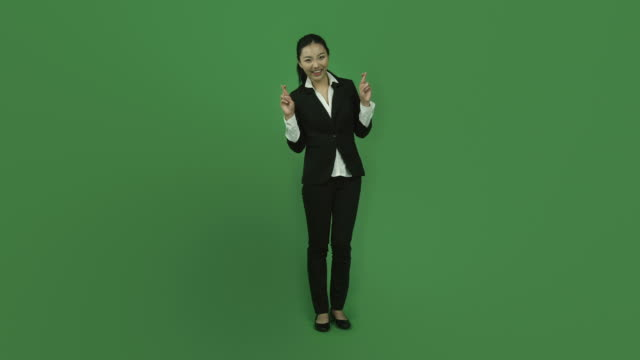 Asian business woman isolated greenscreen green background fingers crossed video