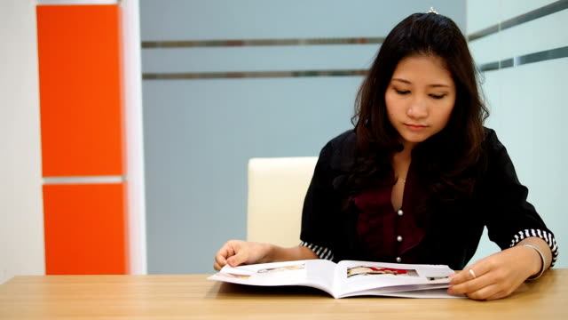 stockvideo's en b-roll-footage met asian business woman reading a magazine - woman home magazine