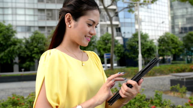 Asian Business Woman Reading with Tablet at Outdoor video