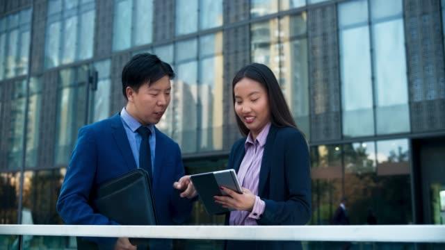 stockvideo's en b-roll-footage met ds aziatische zakenvrouw praten met haar aziatische mannelijke collega tijdens het scrollen de tablet in de voorkant van de business building - mid volwassen vrouw
