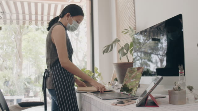 Asian business woman wearing protective mask and work from home with cleaning tablet and computer on table.Concept of social distancing is infection control action to stop the spread disease of Corona virus.4k Slow motion.