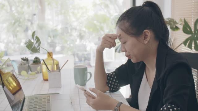 asiatische geschäftsfrau arbeiten von zu hause aus mit smartphone und laptop auf dem tisch mit online-schlechten nachrichten. konzept der sozialen deistancing, um die ausbreitung seuchen des corona-virus zu stoppen.4k uhd. zeitlupe. - smartphone mit corona app stock-videos und b-roll-filmmaterial