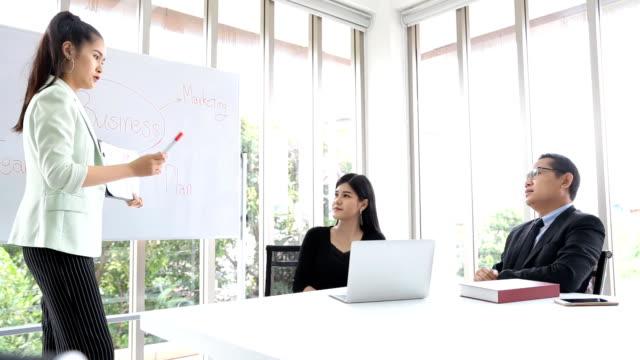vídeos de stock, filmes e b-roll de treinador de mulheres de negócios asiáticos dando apresentação na conferência sobre o quadro branco - assistente jurídico
