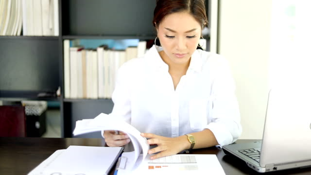 Asian business women using notebook and smiling happy for working video