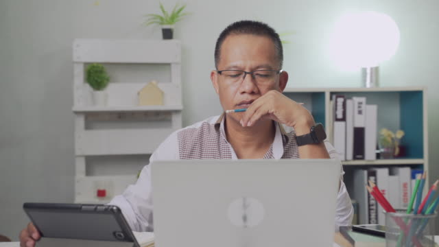 Asian businessman aged 40-50 thinks and analyzes something while working at home.