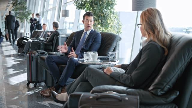 stockvideo's en b-roll-footage met ds aziatische zakenman en een kaukasische zakenvrouw praten in de business lounge op de luchthaven - vliegveld vertrekhal