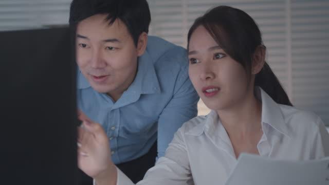 ビジネスプロジェクトの説明を議論するデスクトップコンピュータ画面を見ているアジアのビジネスマンとビジネスウーマン - パソコン 日本人点の映像素材/bロール